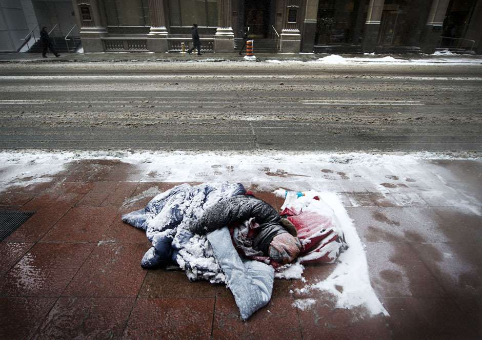 TORONTO, ONTARIO: JANUARY 22, 2013 -- HOMELESS WINTER -- A man is covered in snow while sleeping on the sidewalk in Toronto's Financial District as temperatures dip to -25 degrees with windchill on Tuesday, January 22, 2013.   (Darren Calabrese/National Post)    //NATIONAL POST STAFF PHOTO